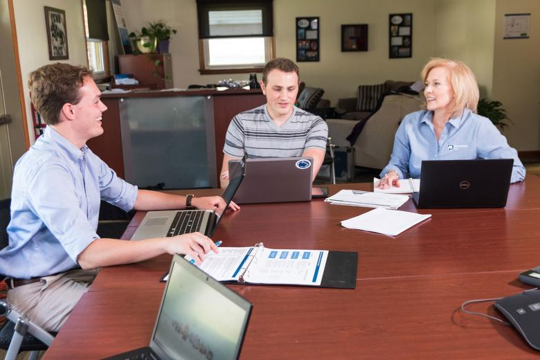 A faculty member and students meet at a conference table.
