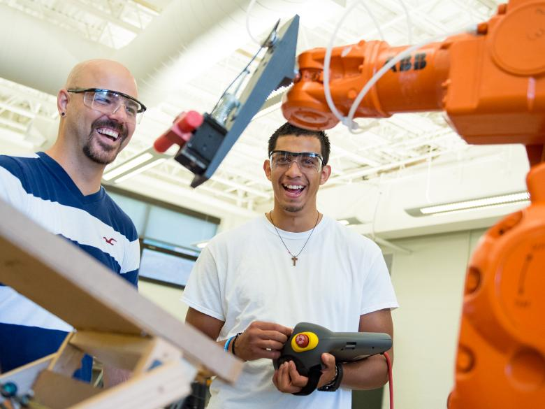 Students working with a robotic arm in an engineering lab.