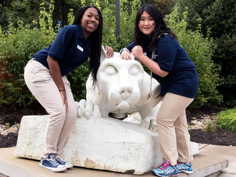 Two Lion Ambassadors pose with the Nittany Lion statue