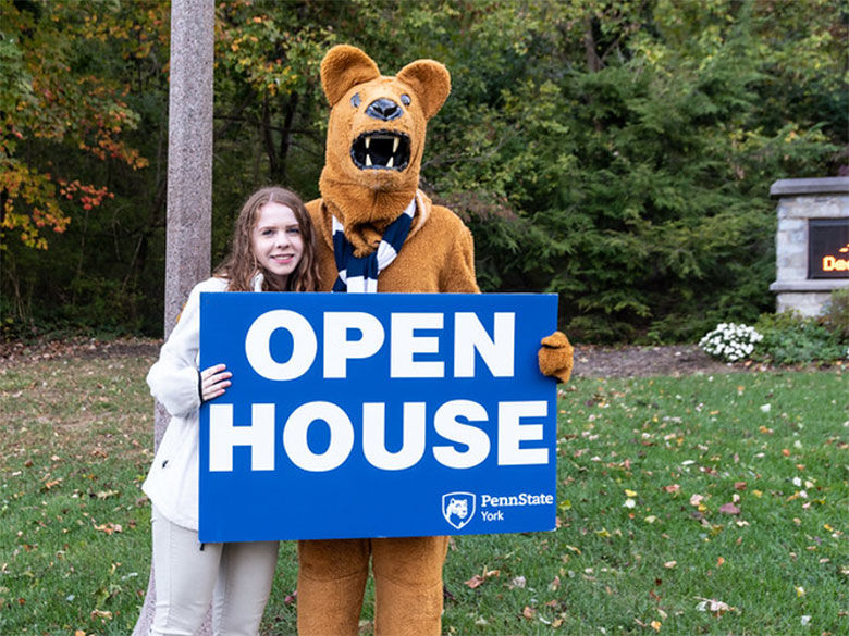 Student and Nittany Lion mascot holding an Open house sign