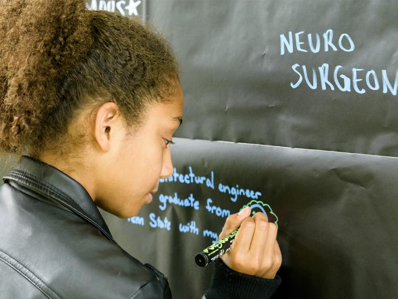 A student writing on the chalk wall during Pathways 2016.