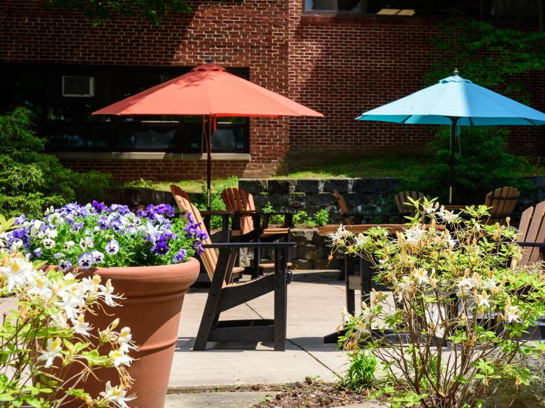 Tables with umbrellas and flowers in a courtyard.