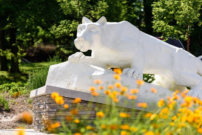 Nittany Lion Statue behind some orange summer flowers.
