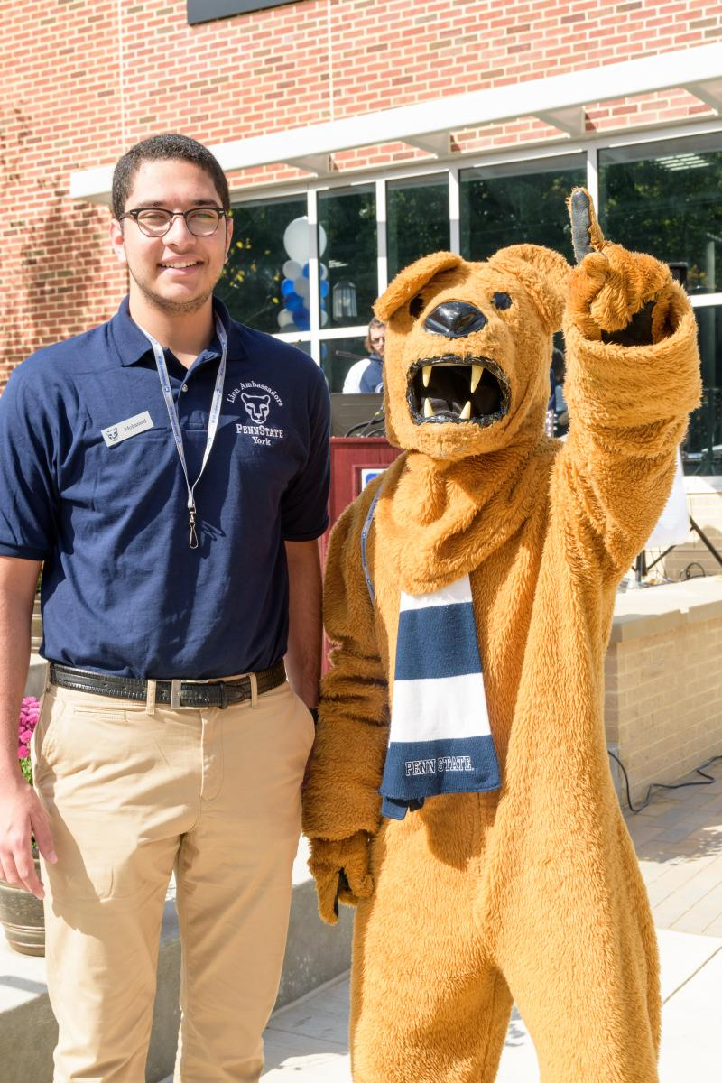 Mohamed El Sonbaty standing with the Nittany Lion mascot.