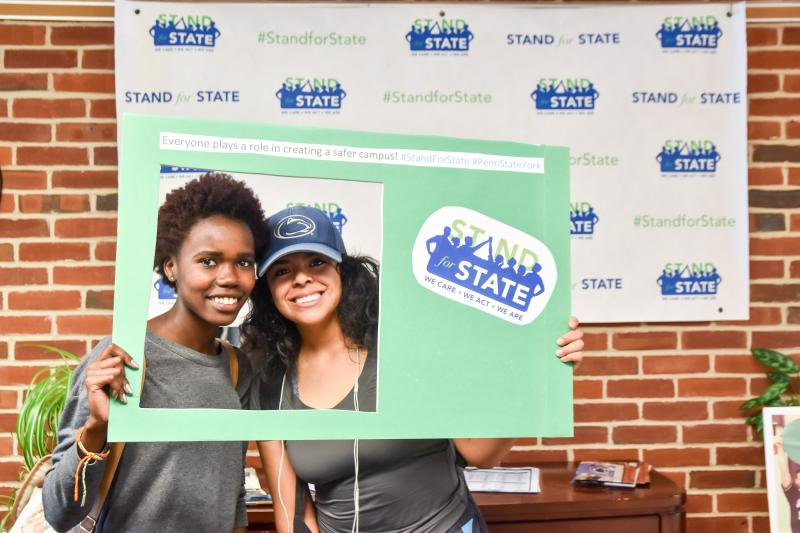 Students pose with Stand for State materials.