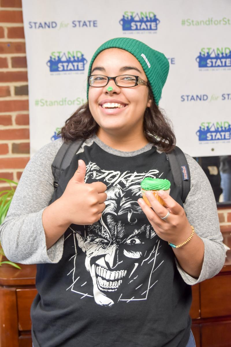 A student with a green cupcake during a Stand for State event.
