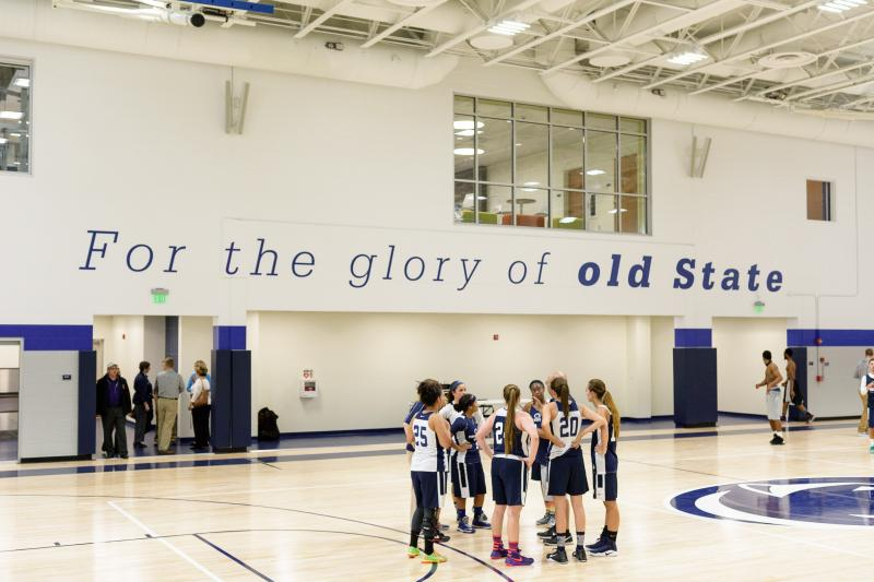 Penn State York Women's Basketball huddling in the middle of the gym.