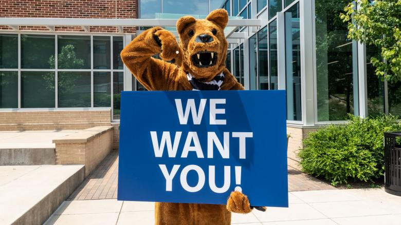 Nittany Lion holding a We Want You! sign.